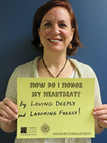 "Photo of Jeanne Smoot holding a sign that reads ""How do I honor my heartbeat? By loving deeply and laughing freely!"""