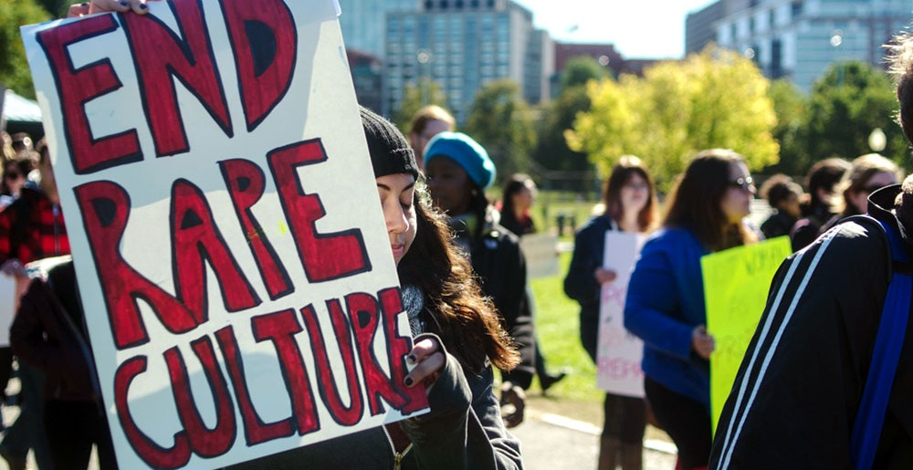 "Image of people walking holding signs, one of which reads ""End Rape Culture""."