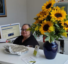 A smiling woman sitting at a desk by a computer with a vase of sunflowers.