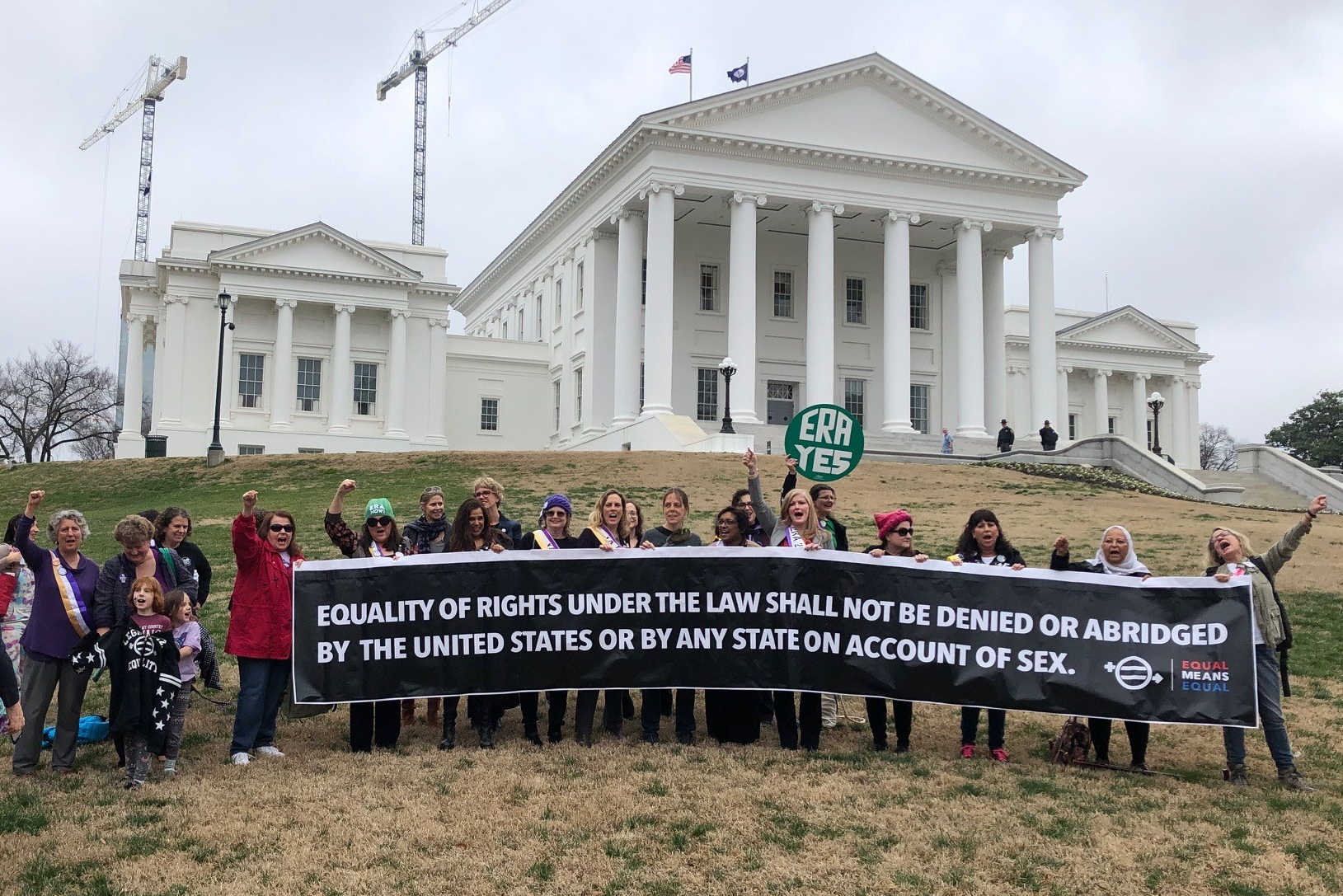 "Group of a couple dozen people with arms raised in victory behind a long banner that reads, ""Equality of Rights Under the Law Shall Not Be Denied or Abridged by the United States or by Any State on Account of Sex"" standing in front of the Virginia State Capitol."
