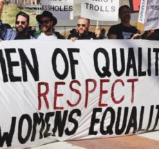 "Photo of protesters holding a banner that reads ""Men of quality respect women's equality."""