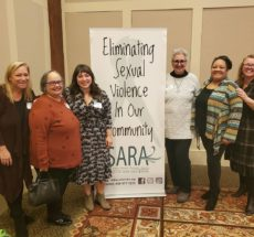 "Photo of six Action Alliance staff standing by a banner that reads ""Eliminating sexual violence in our community""."