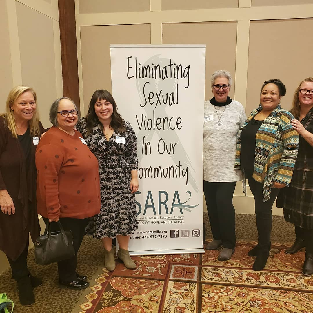 """Six people standing around a banner that says, """"eliminating sexual violence in our community- SARA"""""""
