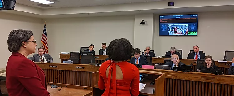 Fatima Smith stands at a podium testifying before a group of legislators dressed in suits with Sen. Jennifer McClellan by her side.