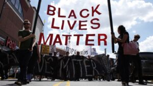 Black Lives Matter protest sign in giant red letters in a march.