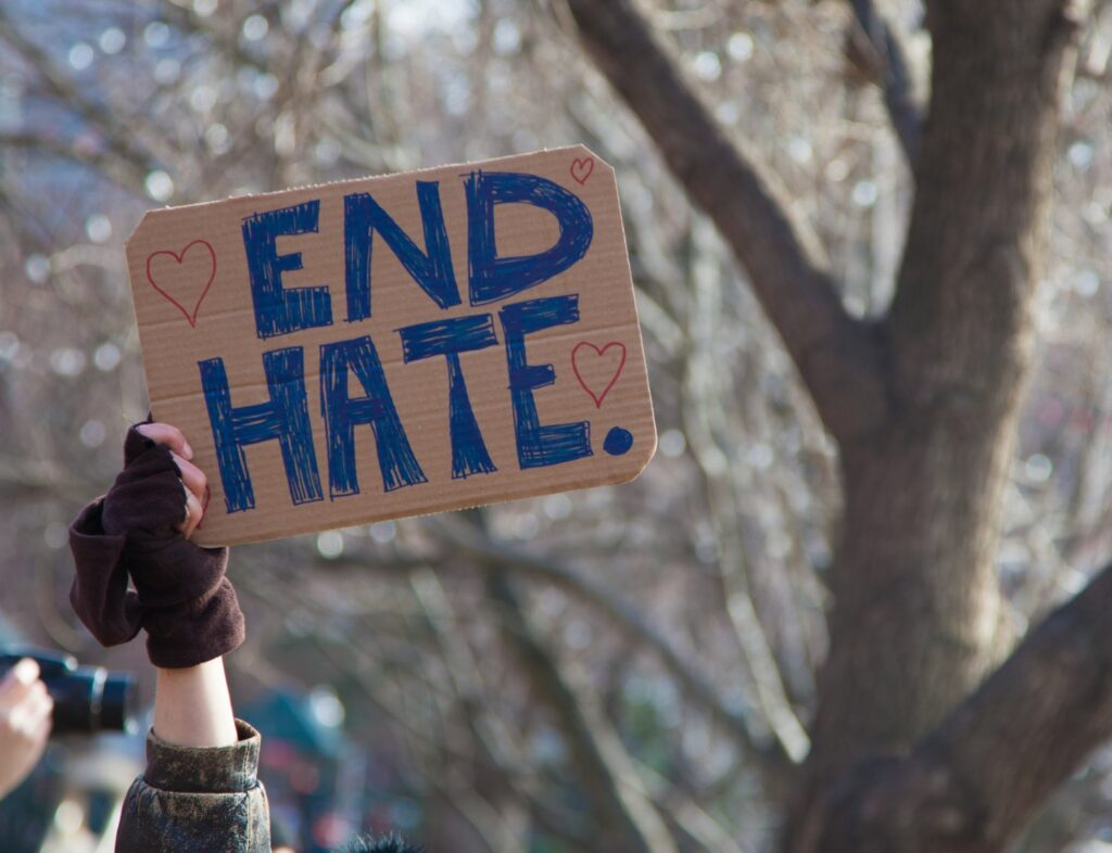 A gloved hand with a sign on brown cardboard that reads End Hate in blue handwritten letters.