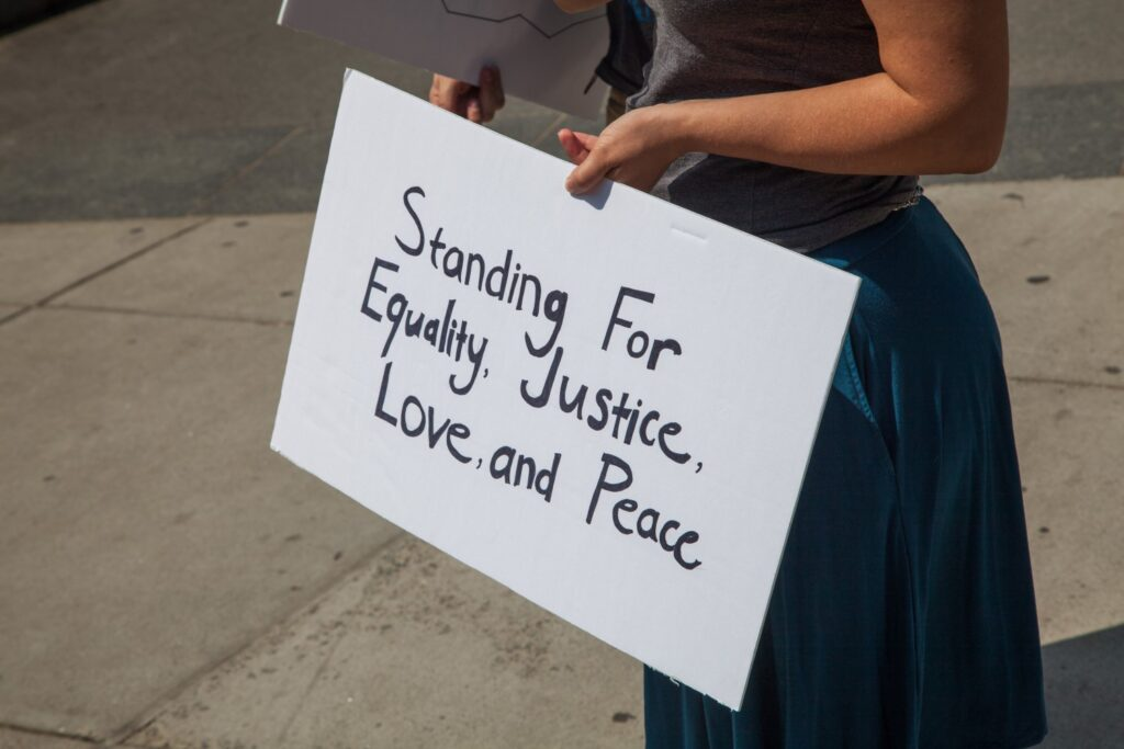 A person holding a white sign with black letters that reads, Standing for Equality, Justice, Love and Peace