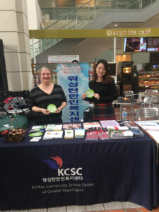 Image of two Korean Community Services Center advocates standing at a booth advertising their agency and holding stickers.