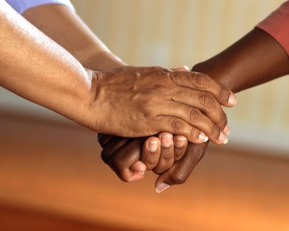 One person's hands holding another's hand in support.