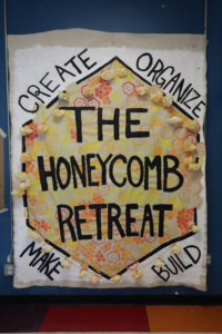 """Picture of a banner which reads """"The Honeycomb Retreat"""" in a yellow and orange hexagon with words along the perimeter which read """"Create, Organize, Make, Build""""."""