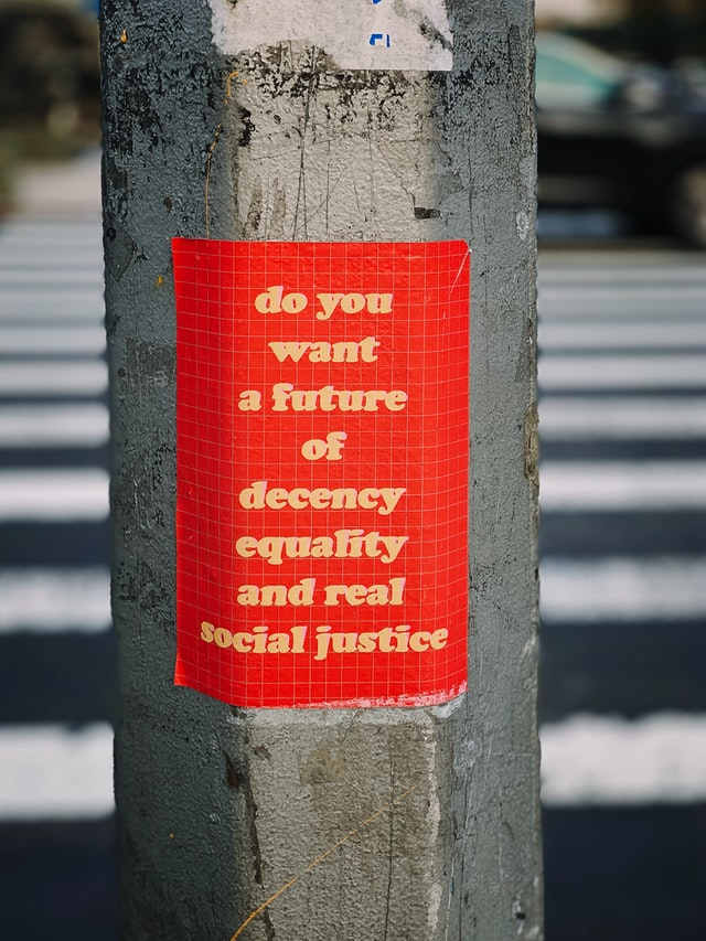 """Street lamp post with red sticker on it with yellow words that read, """"do you want a future of decency, equality, and real social justice."""""""
