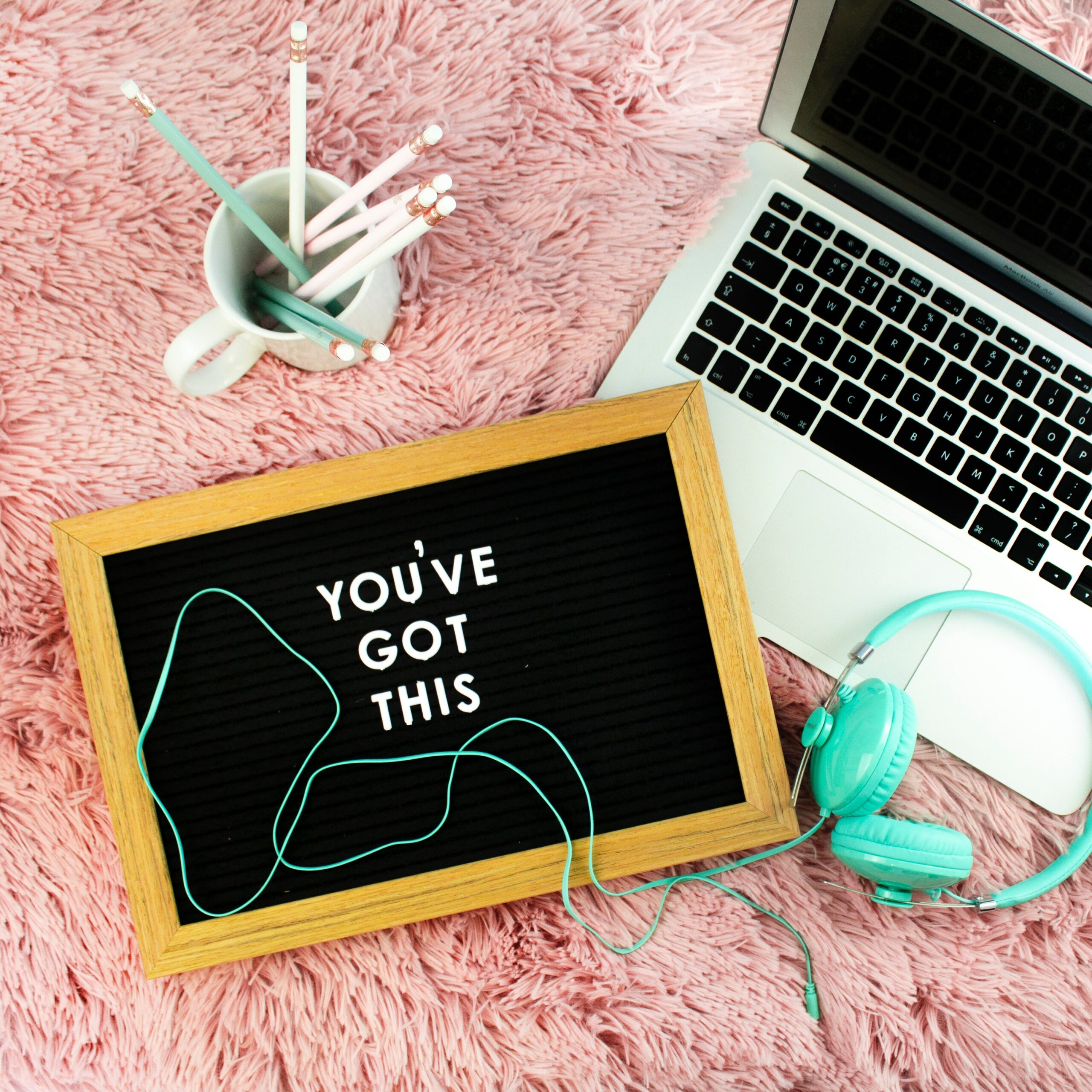 """A laptop with headphones, cup with pencils, and a small chalkboard with the words, """"you've got this"""" written on it."""