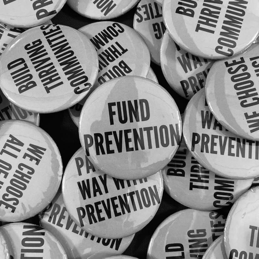 """A grayscale photo of a collection of medium-sized buttons with different phrases, including """"build thriving communities,"""" """"we choose all of us,"""" """"pave the way with prevention,"""" and the central focus is on a button with the words, """"Fund Prevention."""""""