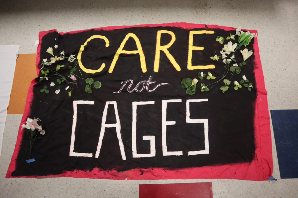 A banner with the words, care not cages on it, with flowers along the edges.