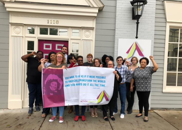 Group of Action Alliance staff in front of the Action Alliance office standing together behind a banner featuring an Angela Davis quote and image.