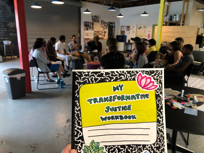 """A hand holding a hand-drawn composition notebook with the title """"My Transformative Justice Workbook"""" in the foreground, with a group of training participants in the background."""