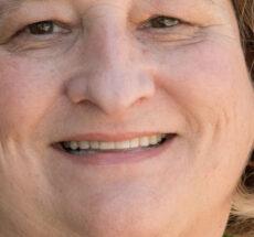 Close up photo of Judy Casteele, smiling.