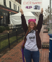"Photo of Katie Moffitt of the Action Alliance holding a sign that reads ""Injustice anywhere is a threat to justice everywhere. -MLK Jr."" and wearing a pink knit hat."