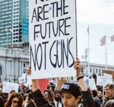 """Photo of protesters, one of whom is holding a sign that reads """"Kids are the future, not guns."""""""