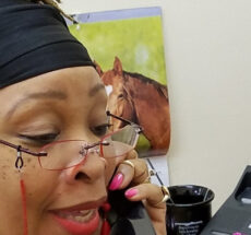 Photo of Charmaine Francois of the Action Alliance answering a phone.