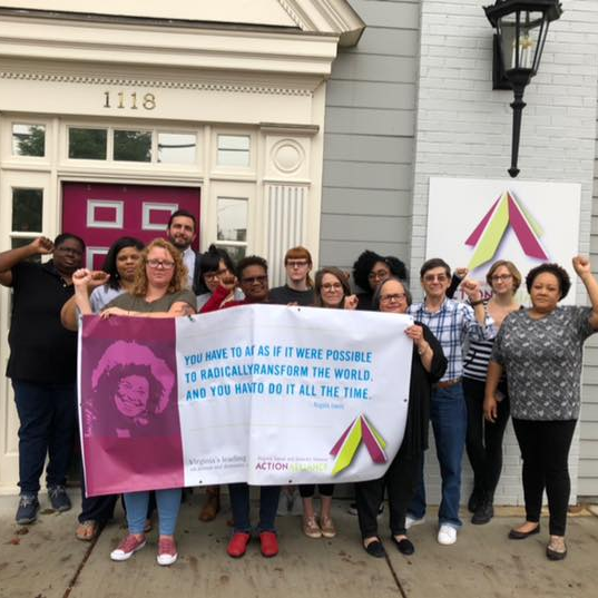 """Photo of a group of people standing in solidarity with fists raised behind a banner with the quote from Angela Davis, """"You have to act as if it were possible to radically transform the world, and you have to do it all the time."""""""