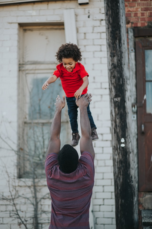 Man wearing purple and red shirt catching a boy wearing a red shirt and blue jeans. Photo by Conner Baker on Unsplash.