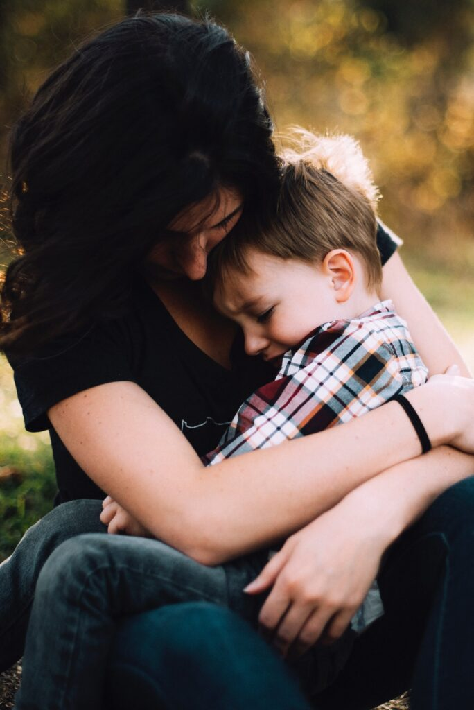 Woman in black t-shirt and jeans holding and consoling a child in red plaid shirt and jeans. Photo by Jordan Whitt on Unsplash.