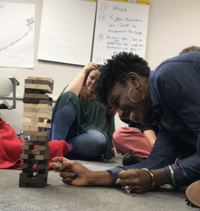 Small group of people sitting in a circle on a carpeted floor looking on as one person is carefully removing a block from the Jenga tower of precariously perched blocks.