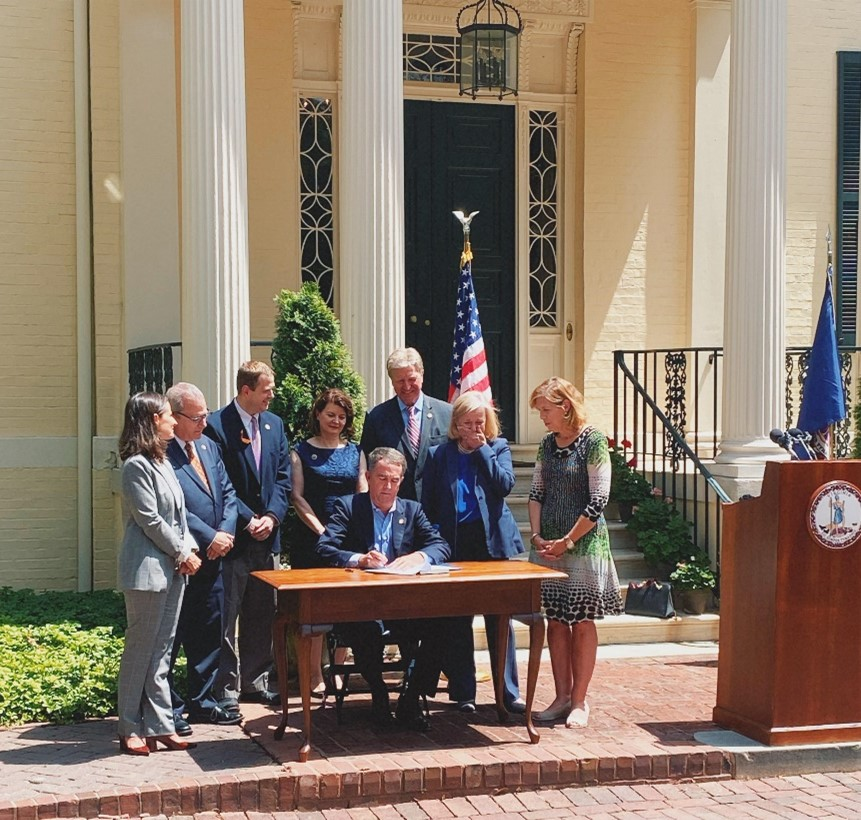 A group of seven men and women in suits and business attire surround Virginia's Gov. Northam as he signs into law HB 1992. Among the seven people is Del. Kathleen Murphy who cries tears of joy. The group is on a red brick sidewalk with the flags of the United States and Virginia in the background.